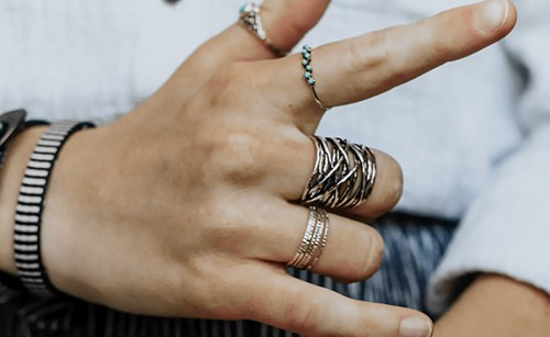 Close-up of woman's hand with stacked rings