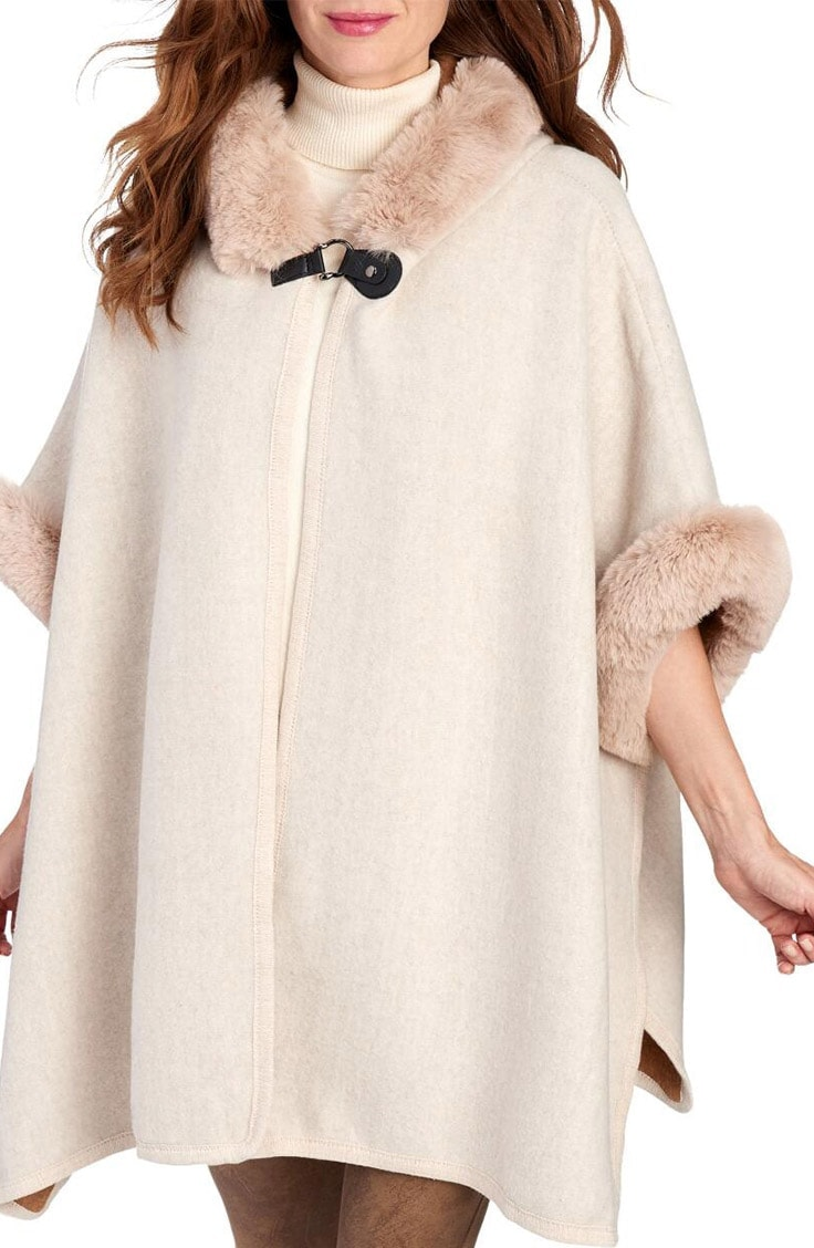 Cream colored cape with fur trim at collar and sleeves