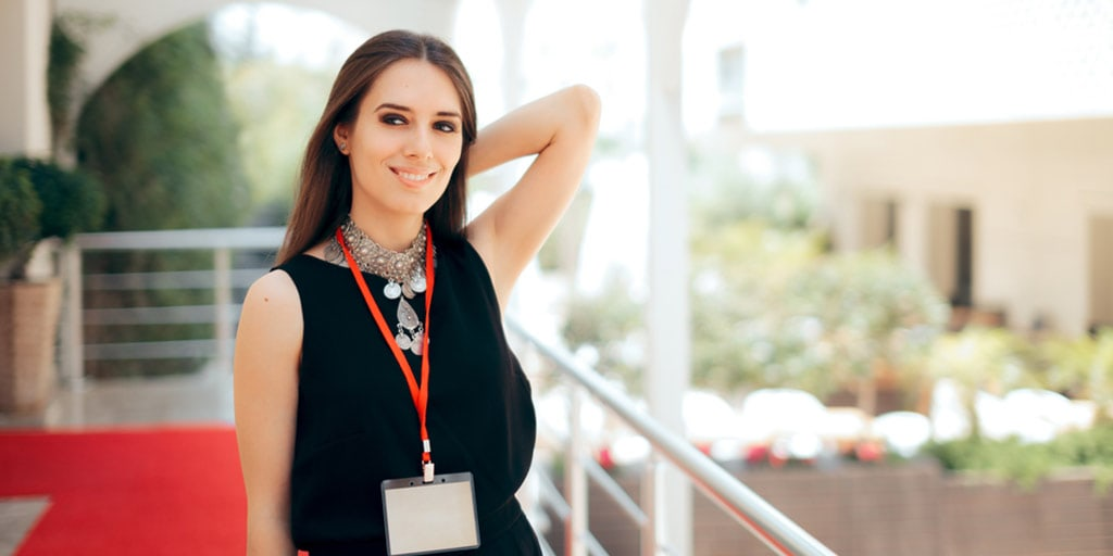 Event planner wearing black dress and statement necklace