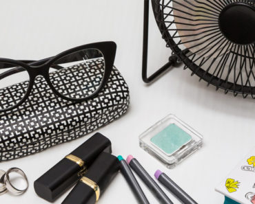 Eyeglasses, eyeglass case and lipstick on a table