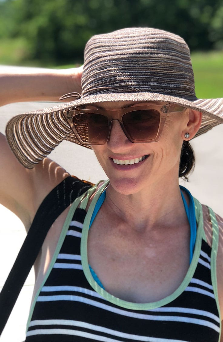 Catherine Brock wearing a floppy hat and sunglasses.