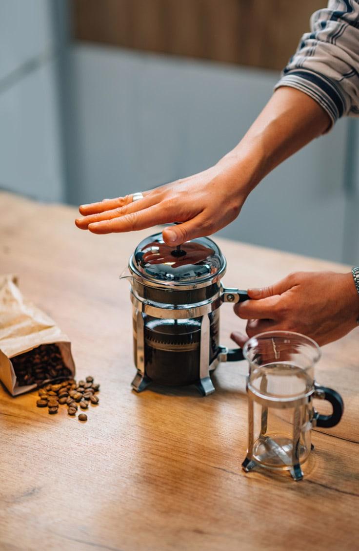 Woman making French press coffee