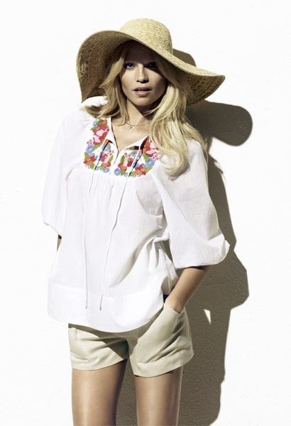 Woman wearing white top with floral detail, floppy hat and shorts
