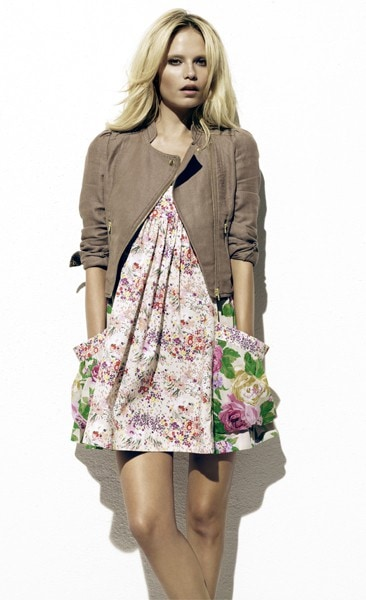 Woman wearing floral dress and brown jacket
