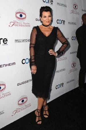 Kris Jenner on the red carpet wearing black evening dress with sheer sleeves
