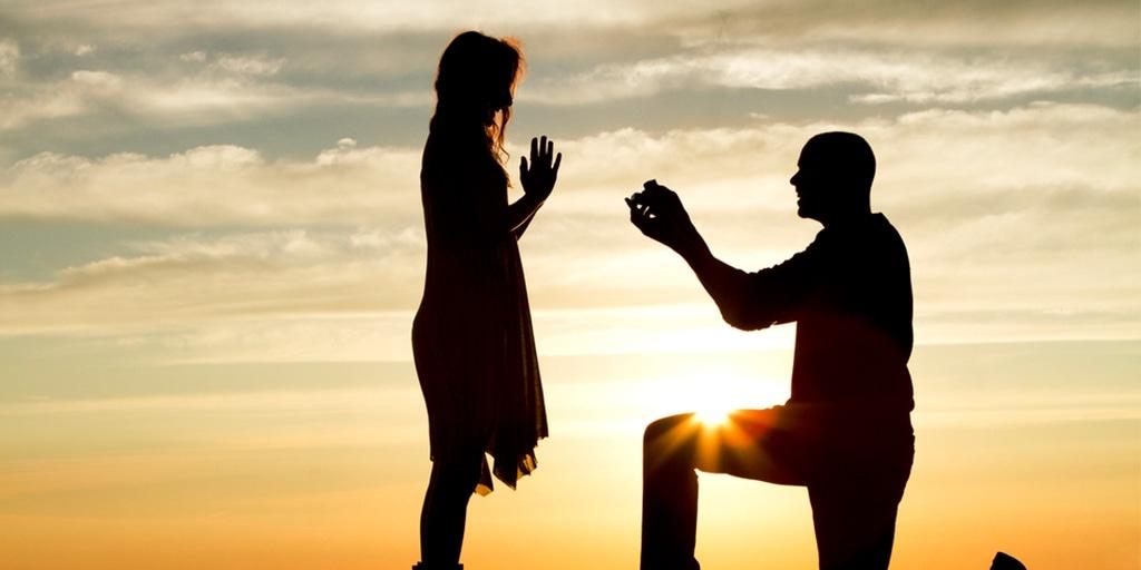 Man proposing to woman at sunset
