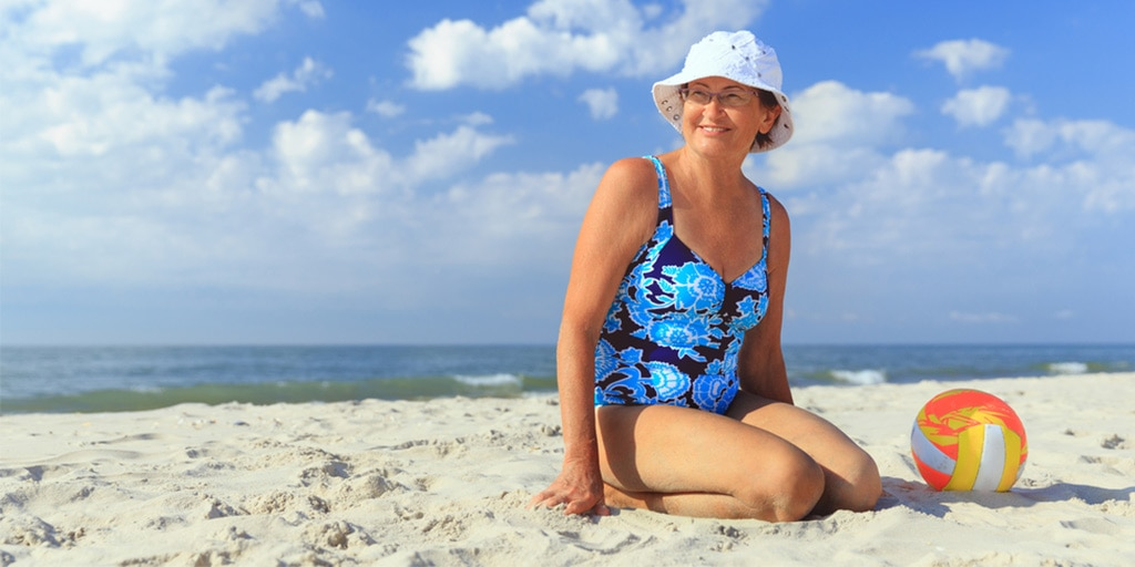 Older woman sitting on the beach in swimsuit