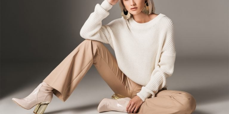 Woman wearing neutral tones and sitting on the floor