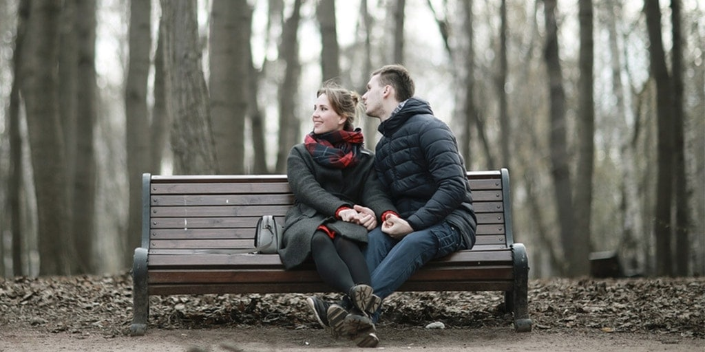Couple sitting on a park bench in cold weather