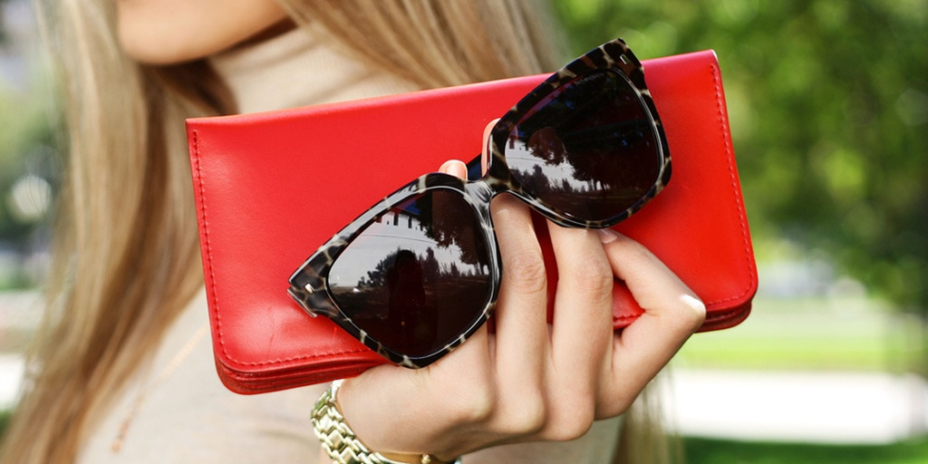 woman holding red wristlet and sunglasses