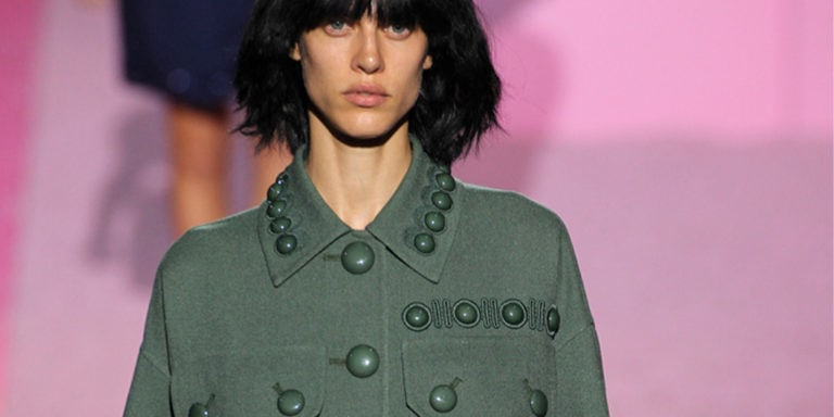 Runway model wearing olive green shirt jacket with buttons
