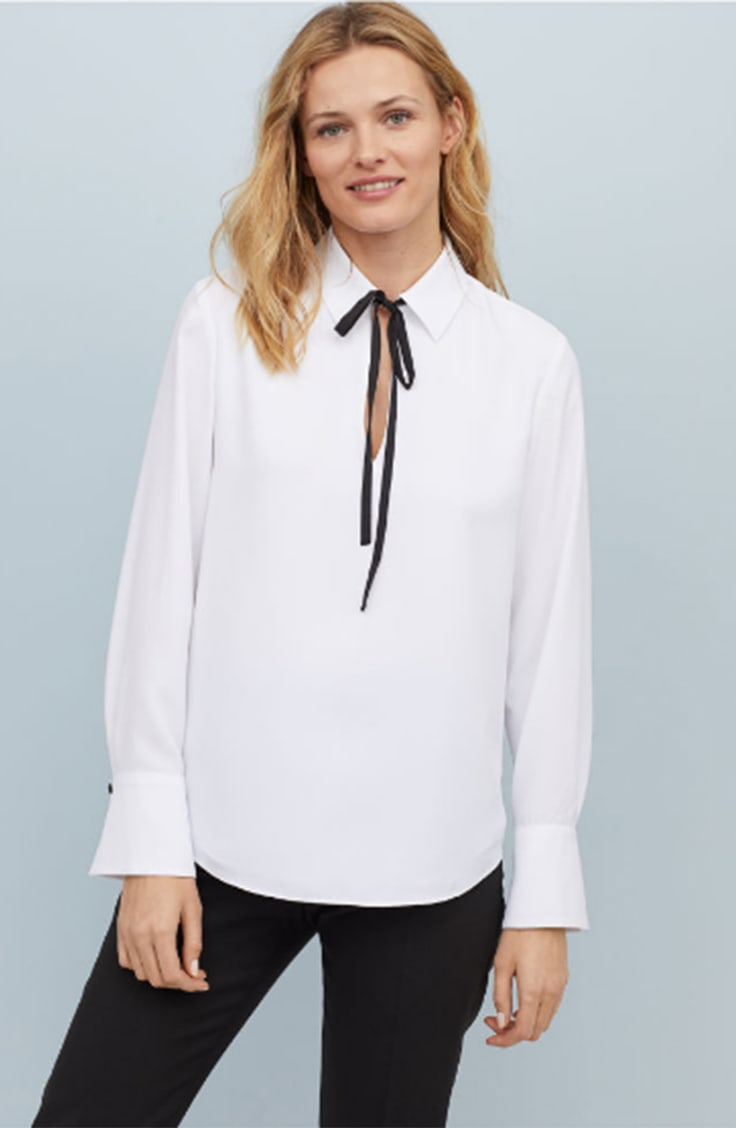 White blouse with black tie at neck