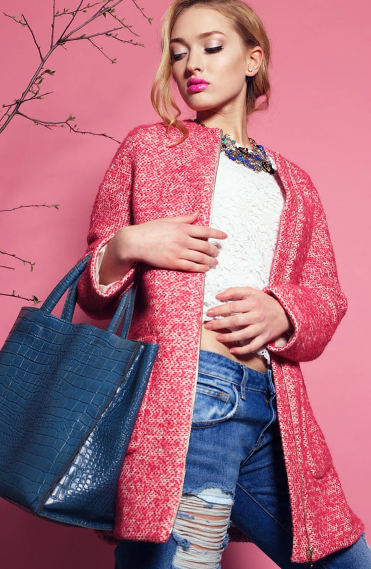 Woman wearing pink jacket with blue bag and distressed denim jeans