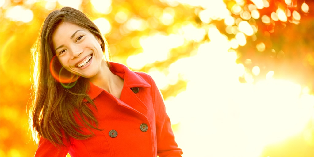 Woman wearing red coat on sunny day