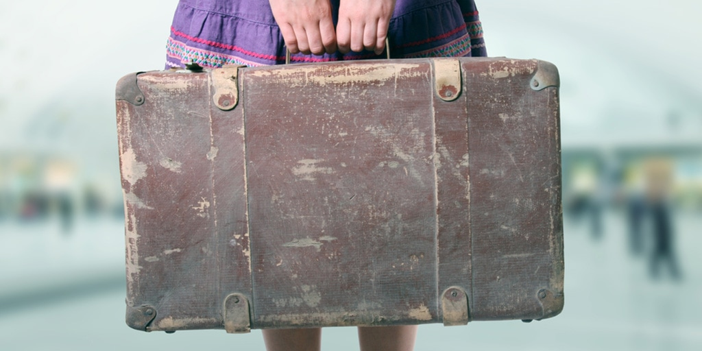 Close up of girl holding suitcase
