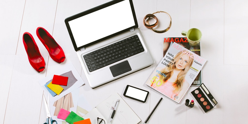 Tumblr fashion blogger's desk: laptop surrounded by magazine, makeup and shoes