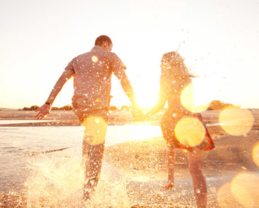Weekend getaway outfits —Couple having fun on the beach