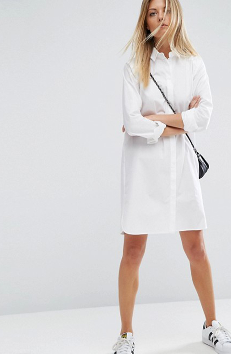 Woman wearing white shirt dress and sneakers