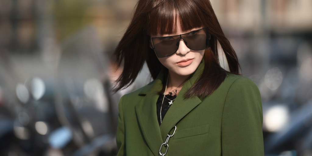 Woman on the street wearing fashion sunglasses and green suit