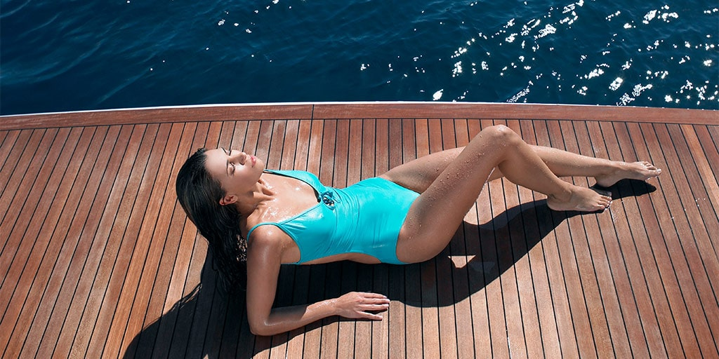 Woman wearing swimsuit on wood deck