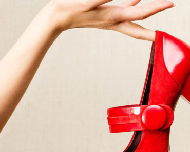 woman holding red patent leather shoes