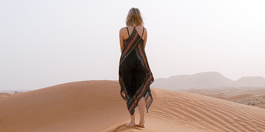 Woman wearing handkerchief hem dress on sand dunes