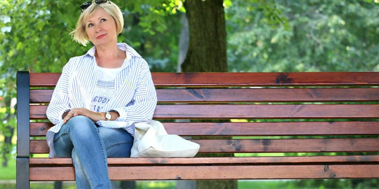 Older woman sitting outside on bench