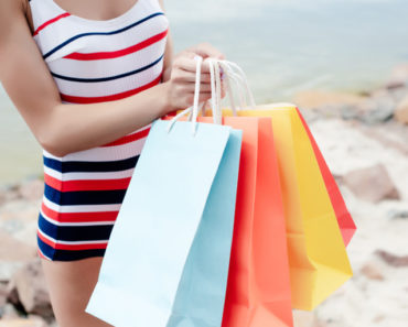 Tall woman wearing swimsuit on beach holding shopping bags
