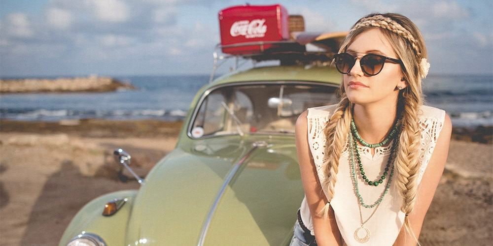 Girl wearing 70s style clothes sitting on VW bug