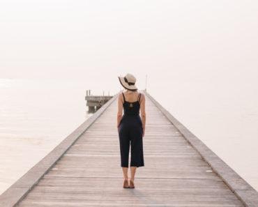 Stylish woman standing on pier