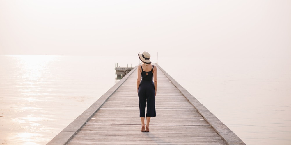 Stylish woman standing on pier