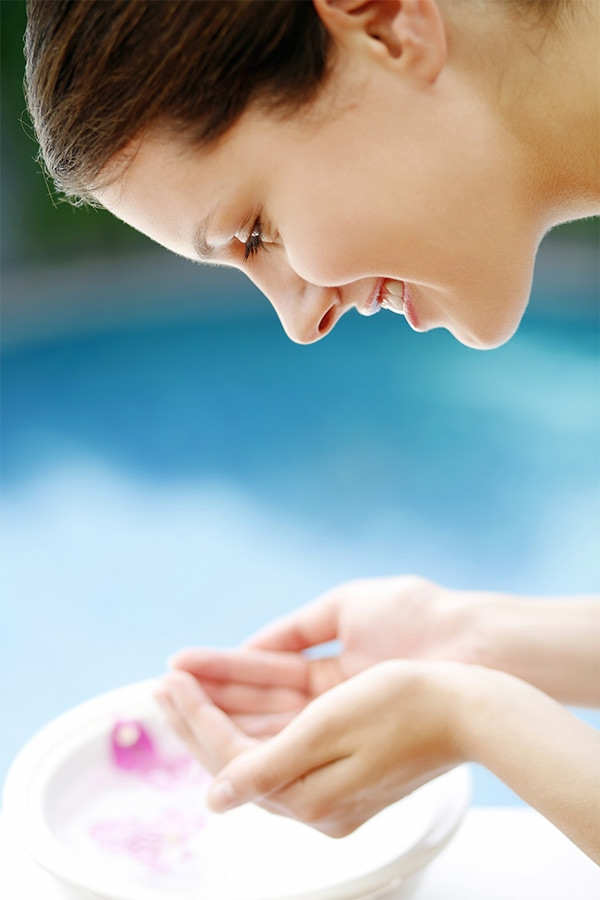 Woman splashing face after olive oil face scrub