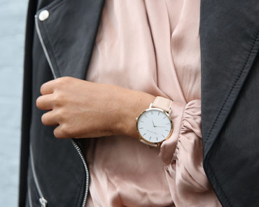 Woman wearing silk top, leather jacket and watch