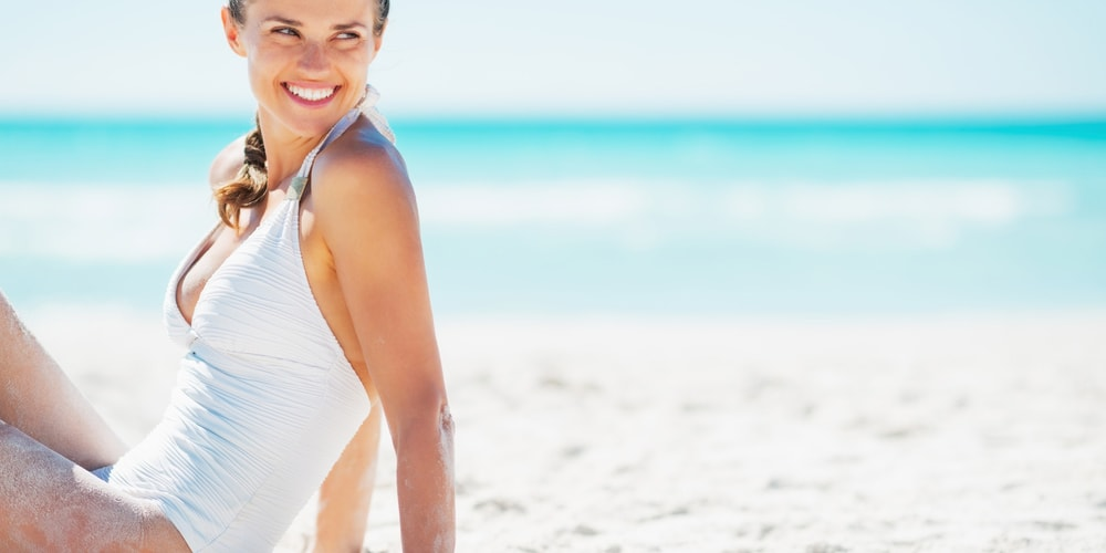 Woman sitting on the beach and smiling