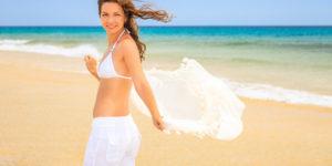 Woman wearing white beach pants