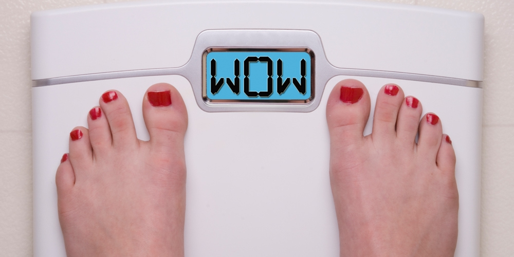 Woman standing on scale, checking her weight