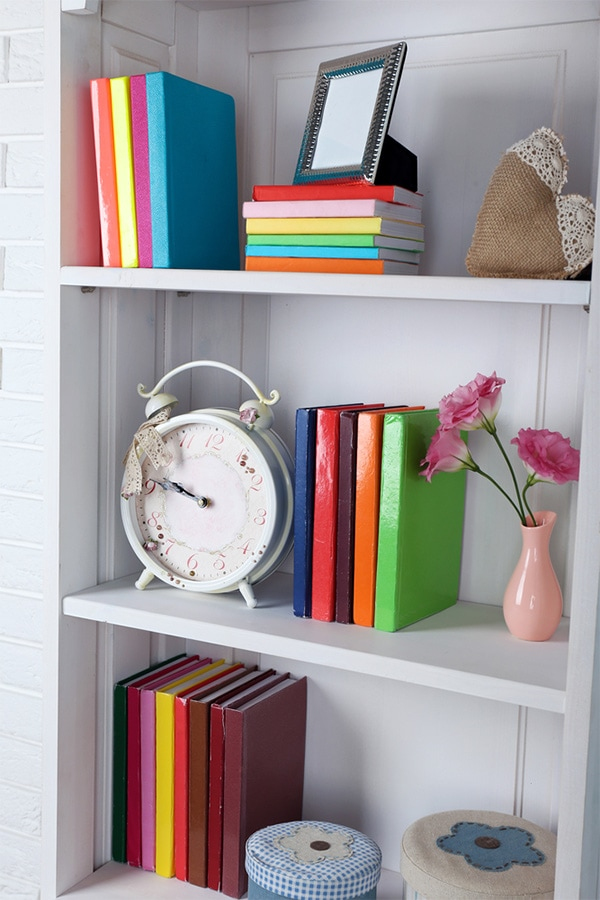 Bookshelf with colorful books and vases.