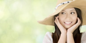 Smiling woman wearing floppy hat outside