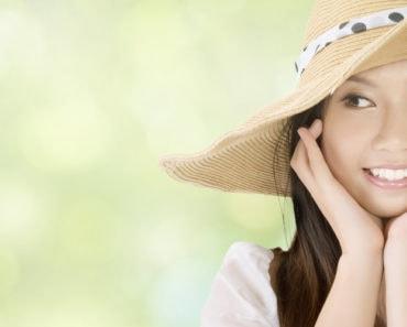 Smiling woman wearing floppy hat outside