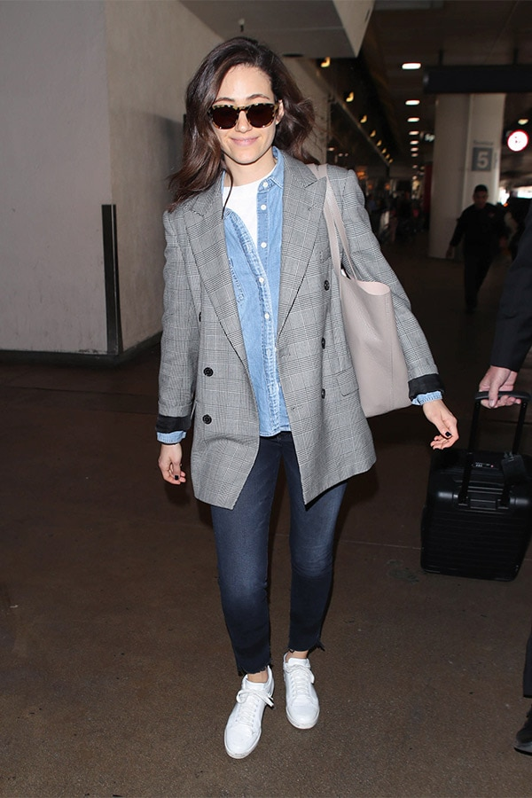 Emmy Rossum in an airport wearing a layered outfit.