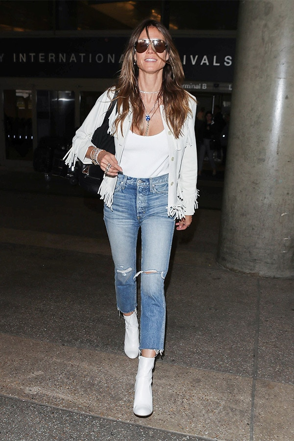 Heidi Klum wearing jeans and fringed jacket in the airport
