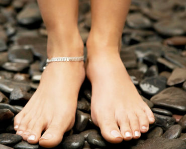 Jewelry for summer -- woman wearing anklet and standing on stones