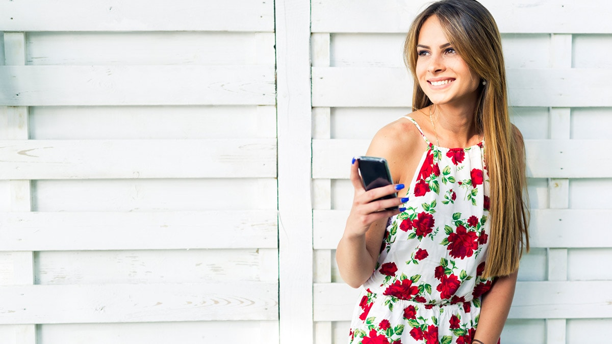 Woman wearing summer dress and holding her phone