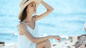 Woman wearing white summer dress on the beach