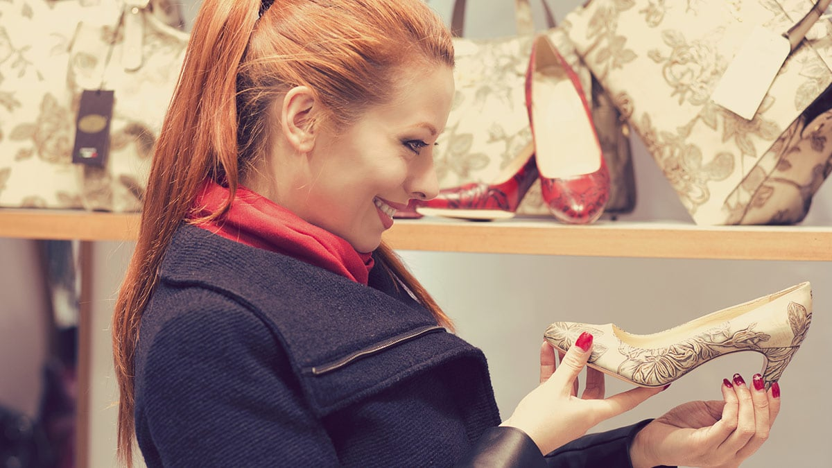 Woman holding a pair of designer shoes