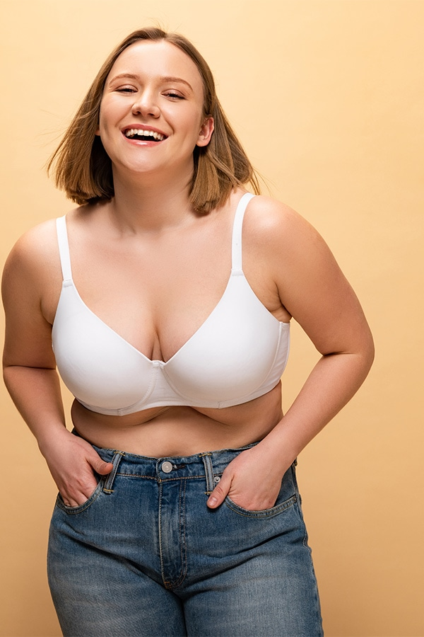 Smiling woman wearing bra and jeans