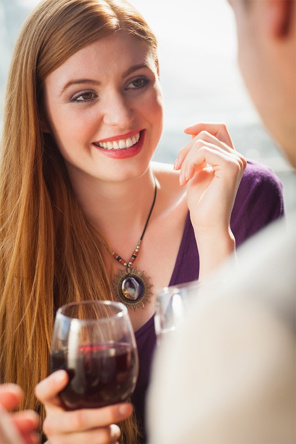 Woman sipping wine at office holiday party