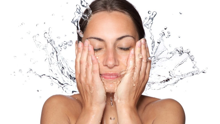 Woman washing her face with water