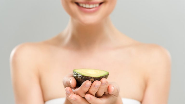 Woman on beauty diet holding avocado
