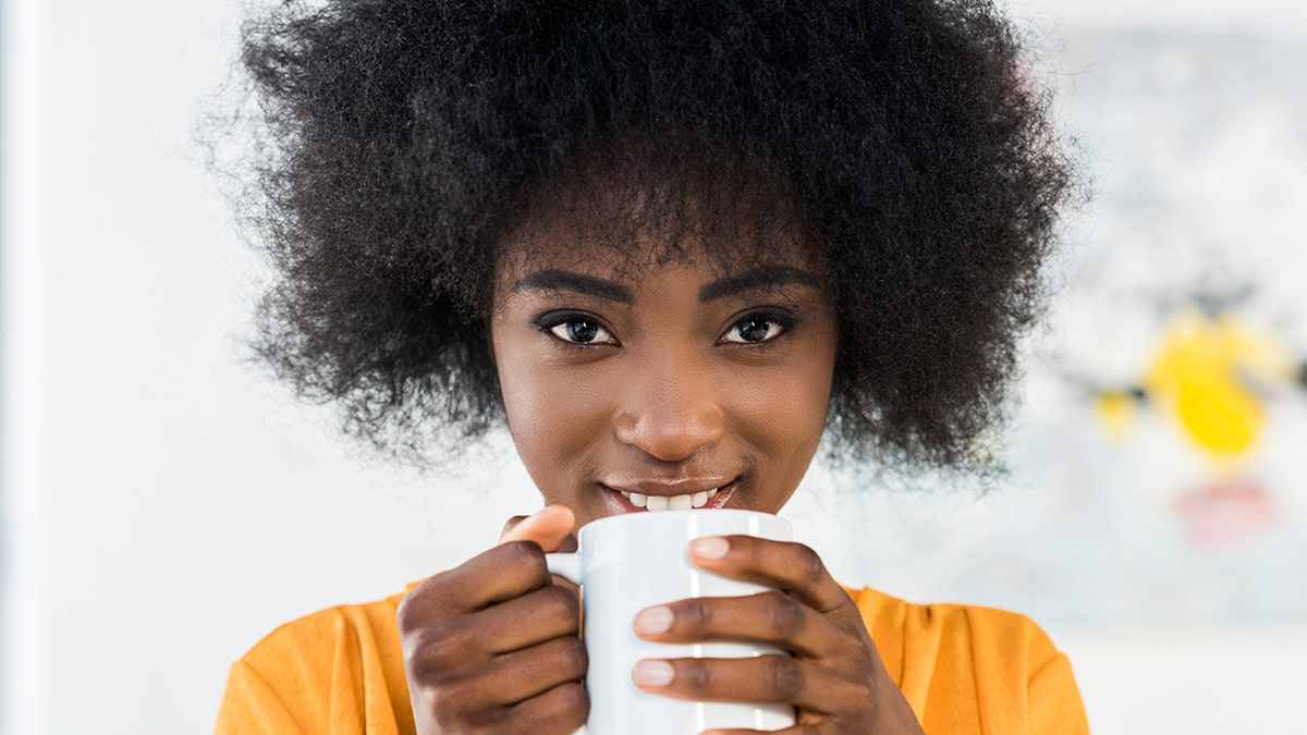 Woman drinking coffee to indulge in cheap treat